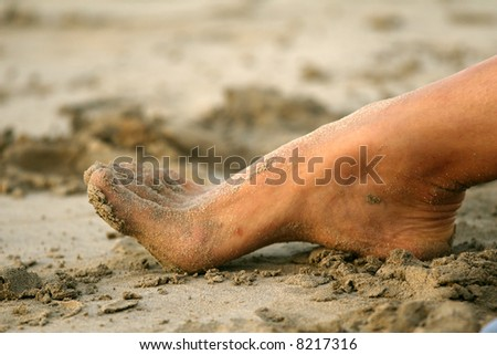 Foot in sand on the beach in caribbean