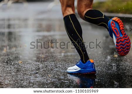 c58003ad8 foot men runner in compression socks running on rain asphalt on water