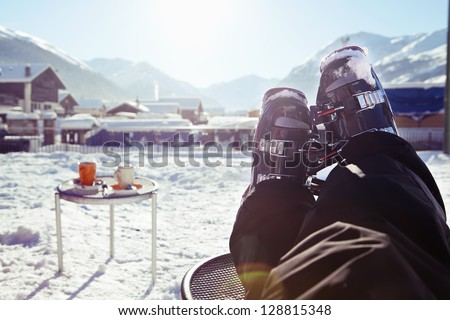 Foot of a skier wearing ski boots, sitting and having rest in a cafe at the sun in front of winter mountains and village panorama