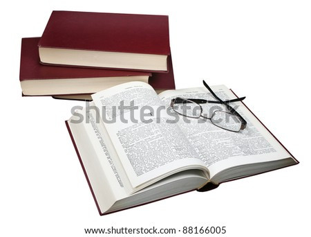 Foot of books and the opened book with a magnifier on a white background