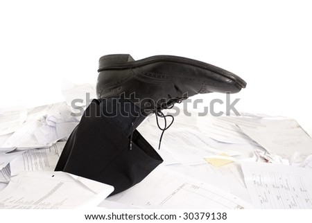 foot of business man sticking out of a desk full of papers