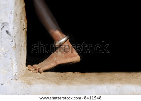 foot of dark asian or african woman with ankle bracelet