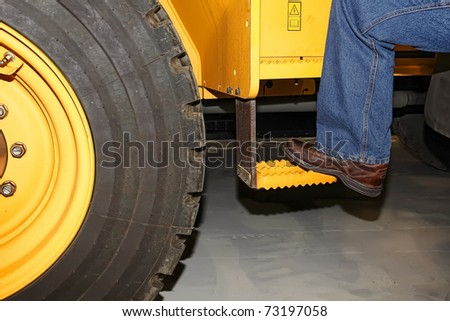 Foot of the tractor operator getting into a tractor #73197058