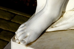 Foot of white beautiful female marble statue close up on dark background