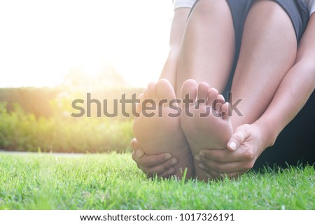 Foot Pain Leg of beauty woman sitting on the road park holding her feet and stretch the muscles in morning sunlight .Health care and spa concept. #1017326191