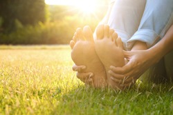Foot Pain Leg of man sitting on grass in the park holding he feet and stretch the muscles in morning sunlight .Health care and spa concept.