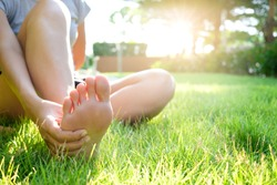 Foot Pain Leg of woman sitting on grass in the park holding he feet and stretch the muscles in morning sunlight .Health care and spa concept.