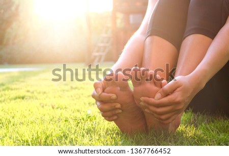Foot Pain Leg of woman sitting on grass in the park holding he feet and stretch the muscles in morning sunlight .Health care and spa concept. #1367766452