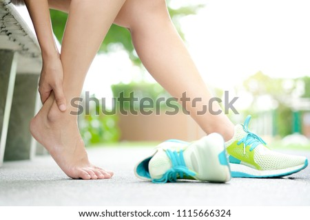 Foot Pain Leg of woman which runner athletic by running shoes sitting on grass in the park holding he feet and stretch the muscles in morning sunlight .Health care and spa concept #1115666324