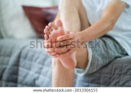 Foot pain, man suffering from feet ache in home interior, podiatry concept