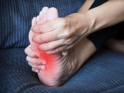 Foot pain, sore feet of young thai asian woman and use hand to massage feet and soles to relieve pain.