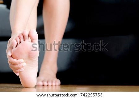 Foot Pain woman sitting  holding her feet.Health concept. #742255753