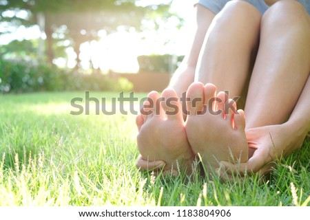 Foot pain .Woman sitting on grass Her hand caught at the foot. Having painful feet and stretching muscles fatigue To relieve pain. health concepts. #1183804906