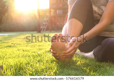 Foot pain .Woman sitting on grass Her hand caught at the foot. Having painful feet and stretching muscles fatigue To relieve pain. health concepts. ストックフォト ©