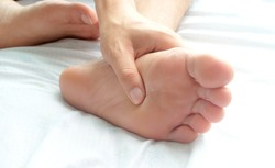 Foot Pain ,young man sitting on the bed at home,  he holding  feet press massage . Concepts of pain and health therapy.