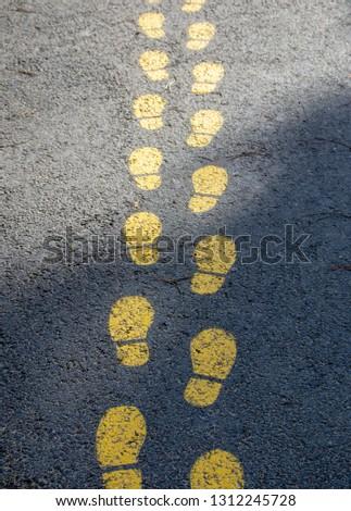 foot pattern on asphalt, indicates the way #1312245728