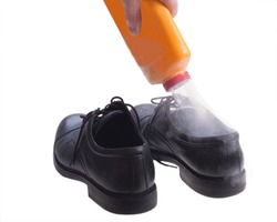 Foot powder being poured into shoe to control odor.