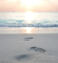 Foot prints at sand in sunrise on tropical beach