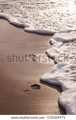 Foot prints at sand in sunset