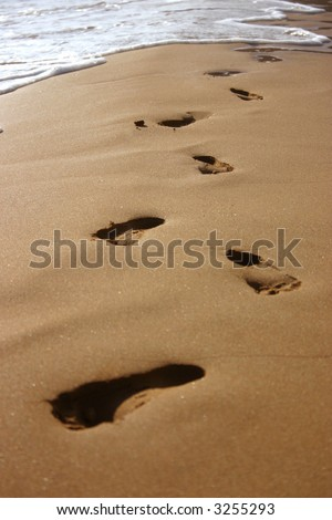 foot prints at the beach soon being washed away by wave