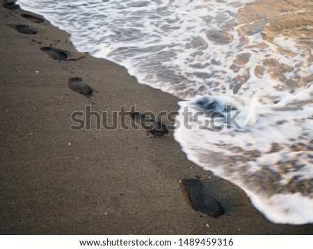 foot prints on a black sand beach with tilt-shift blur. Surf in background. Concept for loneliness, solitude, depression. #1489459316
