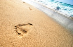 Foot Prints on Tropical Sandy Beach and sea waves in the background