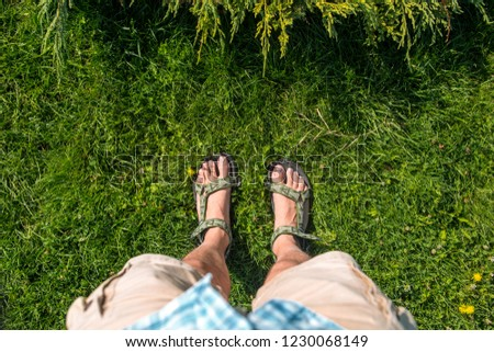 Foot selfie. Top view of feet in summer sandals on green grass background