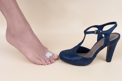 Foot silicone toe separator. Foot in high-heeled shoe. Tired female leg. Valgus on female feet