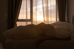 Foot sleeping in the morning at dawn, the girl hangs down the bed. Spy photo. Deep sleep