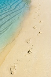 Foot steps and surf on tropical beach - abstract travel background