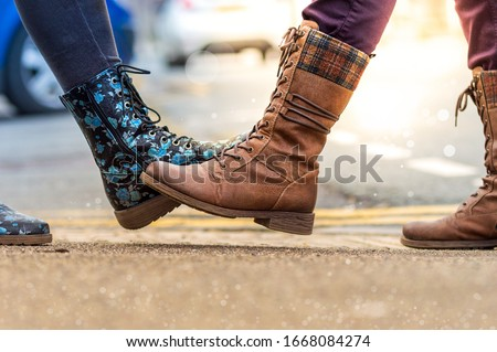 Foot tap. New greeting to avoid the spread of coronavirus. Two women friends meet, instead of greeting with a hug or handshake, they touch their feet together. Filters applied for artistic effect.