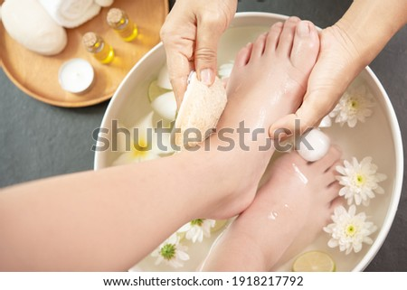 foot washing in spa before treatment. spa treatment and product for female feet and hand spa. white flowers in ceramic bowl with water for aroma therapy at spa.