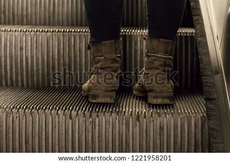 Foot, wearing old boots, standing on escalator step  #1221958201