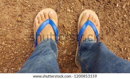 Foot wears blue sandals on the floor. #1200853159