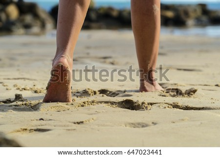 foot woman walking on the sand beach with hot sunlight #647023441