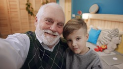 Footage of granddad with gray hair and little boy taking selfie. Modern grandpa using camera, hugging little boy. Men smiling in background of bed. Bedroom.