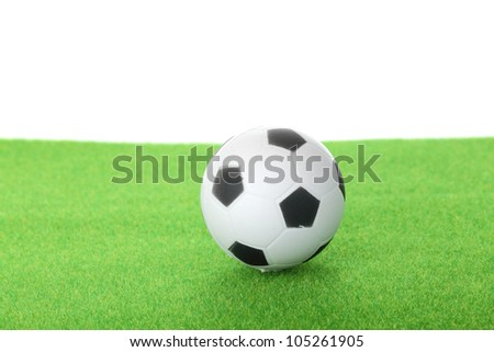 football and green grass on white background