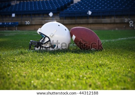 Football and helmet on a field