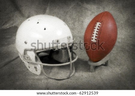Football and helmet on tan studio background with copy space muted texture and tee SOFT FOCUS AND TEXTURE