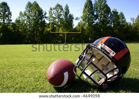 Football and helmet with goal post in background