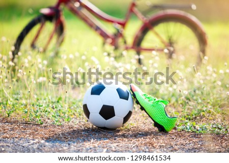 cbf0e61d8 football and soccer shoes with blurry of red bicycle and green grass for  outdoor sport #
