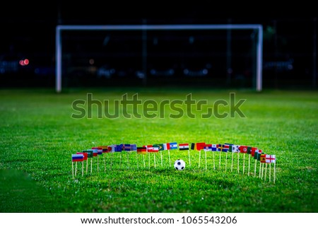 Football ball on green grass and all national flags #1065543206