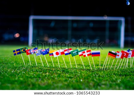 Football ball on green grass and all national flags  #1065543233