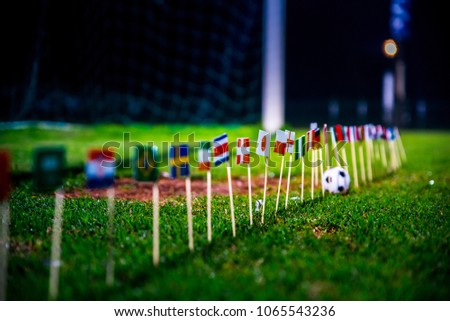 Football ball on green grass and all national flags  #1065543236