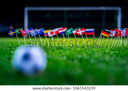 Football ball on green grass and all national flags #1065543239