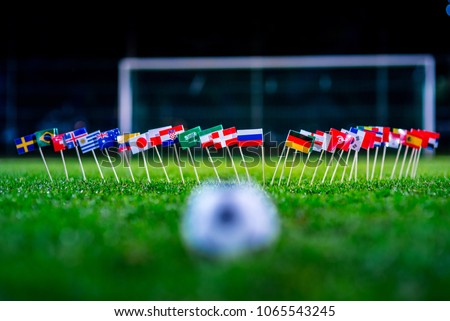 Football ball on green grass and all national flags  #1065543245