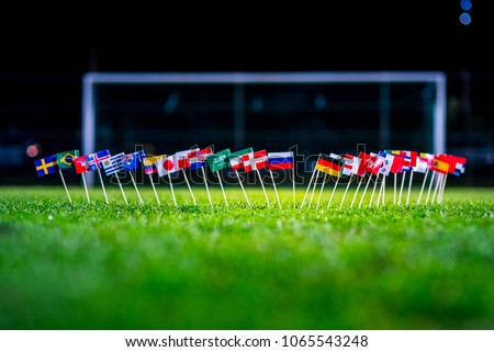 Football ball on green grass and all national flags  #1065543248