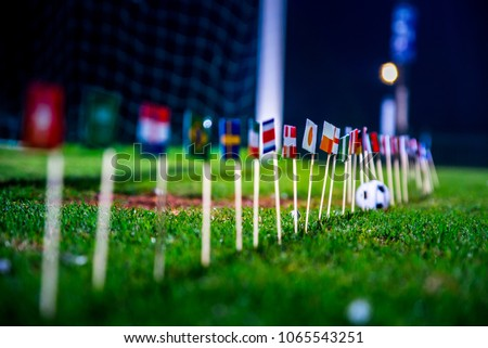 Football ball on green grass and all national flags  #1065543251