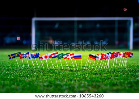 Football ball on green grass and all national flags  #1065543260