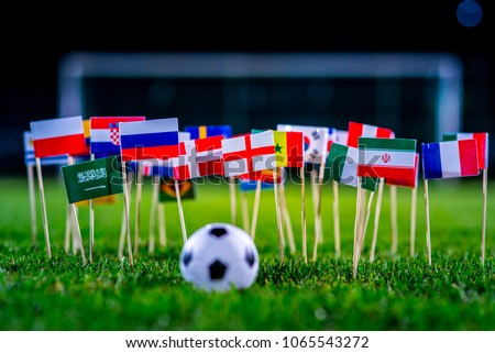 Football ball on green grass and all national flags #1065543272